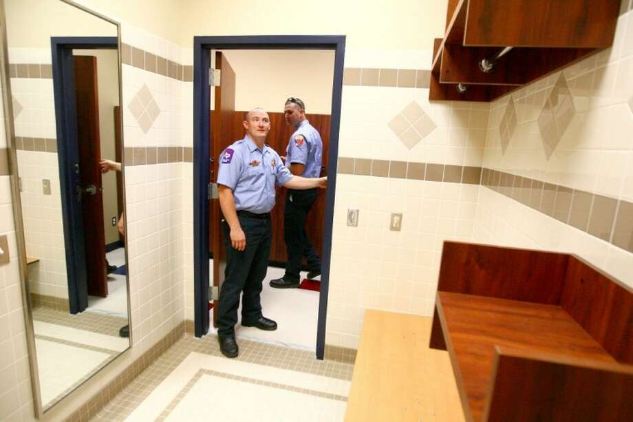 New Caney firefighters tour the showers and locker room during the grand opening of EMS Station 30 in New Caney Thursday. Photo: Staff Photo By Karl Anderson