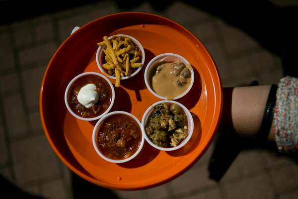 Bay City resident Heidi Grekowicz holds out her samples of chili from the H Hotel on Saturday at the Midland Downtown Business Association's 18th Annual Chili and Salsa Taste-Off. Thirty-three booths dotted downtown as participants sampled various chills and salsas before casting their votes.Saginaw Knitting Mill, Quick Reliable Printing and the Midland Downtown Business Association all sponsored the event.