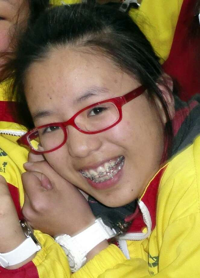 In this undated photo, Ye Mengyuan poses for photos with other classmates in the classroom in Jiangshan city in eastern China's Zhejiang province. Mengyuan was one of three victims of the July 6 crash of Asiana Airlines Flight 214 in San Francisco. On Friday, the San Mateo County Coroner's Office announced that Mengyuan survived the plane crash only to be run over and killed by a firefighter's vehicle.