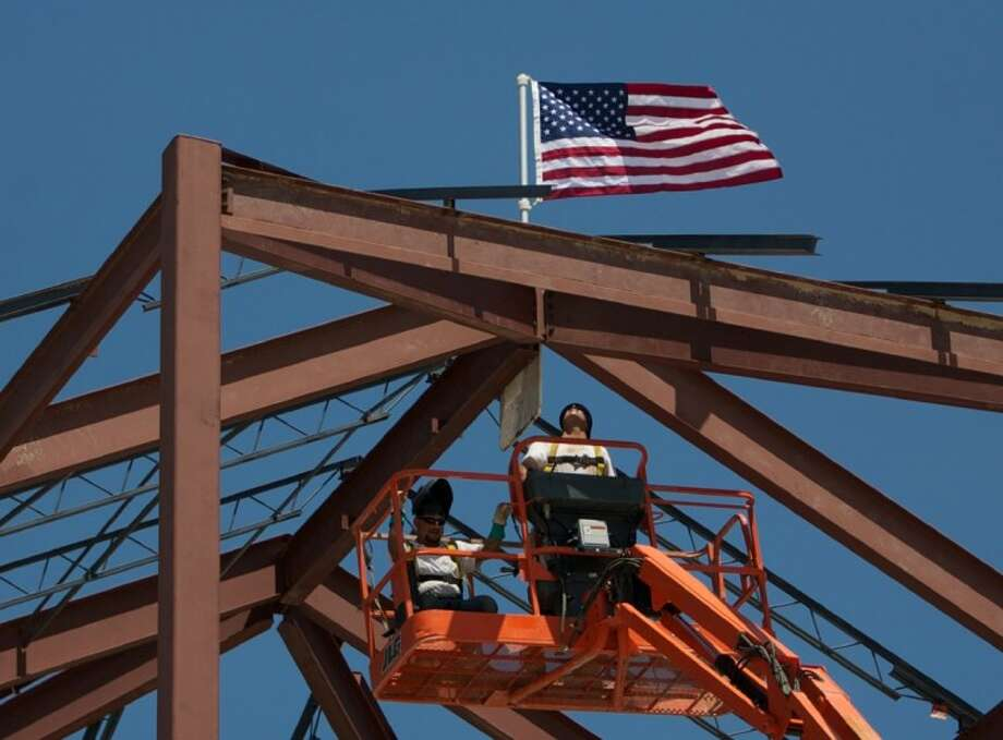"""Jon Nickels, right, and Jose Sorola place a flag at the top of the Central Fire Station during Wednesday's """"top-out"""" ceremony in The Woodlands. Photo: Staff Photo By Eric Swist"""