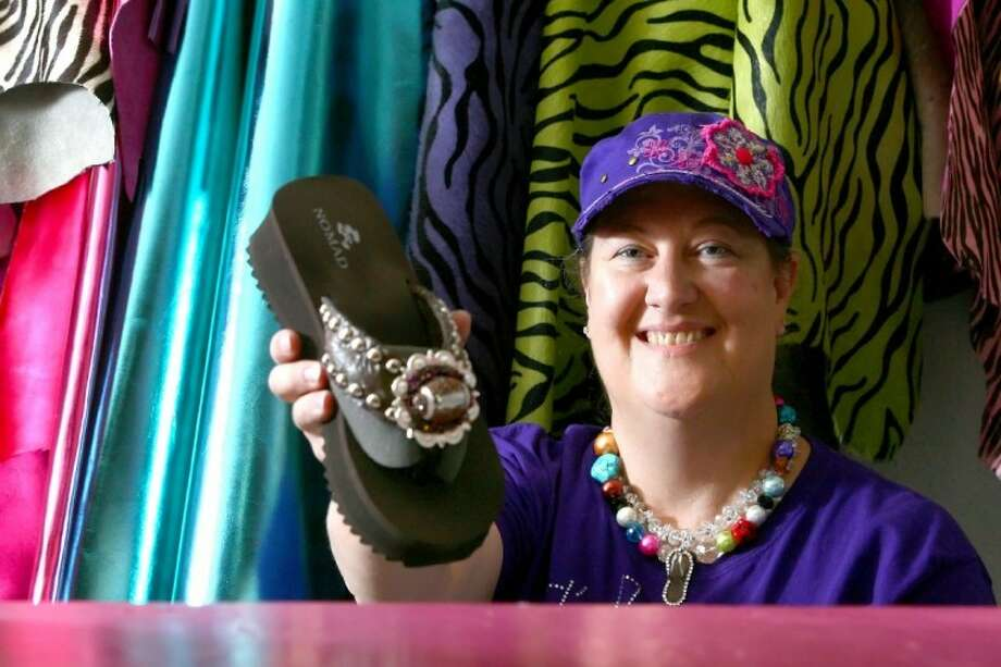 Kim Scholwinski, owner of Flip Flop Bling in Willis, displays one example of this summer's fashion trend. Photo: Staff Photo By Karl Anderson