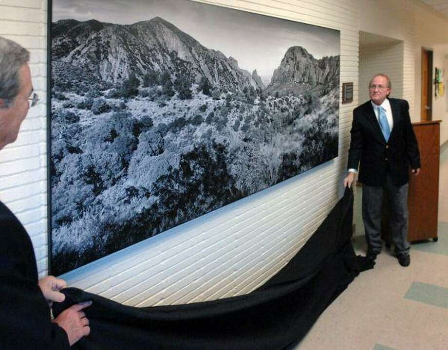 Two representatives from Lamar University undrape a 9-foot-by-4-foot panoramic photograph of Big Bend National Park, taken by Richard Ashmore, geology instructor at Lone Star College-Montgomery. Ashmore was commissioned by Lamar to produce the image.