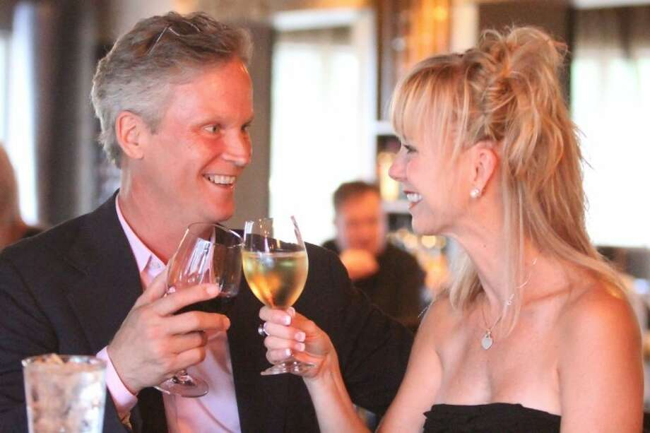 A couple enjoys a toast at the Crush Wine Lounge on The Woodlands Waterway.