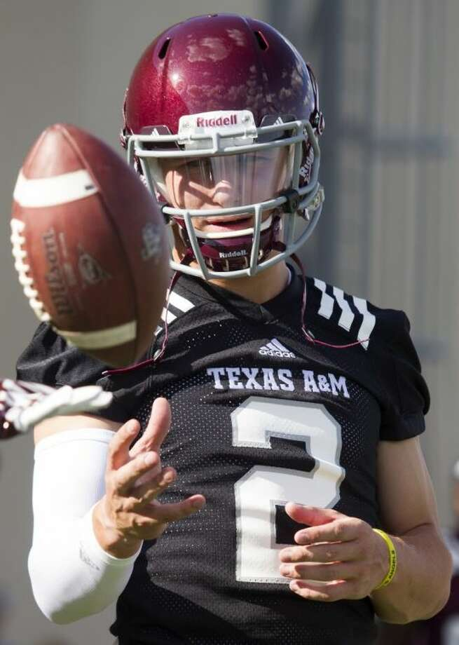 Texas A&M quarterback and Heisman Trophy winner Johnny Manziel warms up before practice on Aug. 5 in College Station. Photo: Patric Schneider