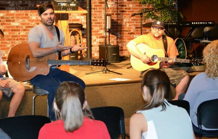 Christian Music Artists David Gentiles, left, and Micah Tyler lead worship Thursday morning at Camp Praise at The Woodlands Methodist Church. Camp Praise was held this week to teach teenagers songwriting, vocals, guitar, piano and how to lead worship in a church setting.