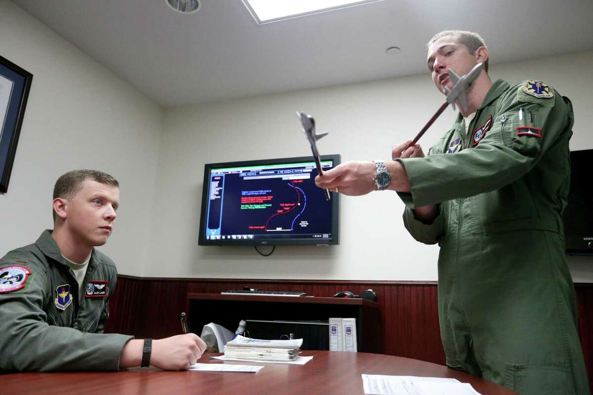 "U.S. Air Force Lt. Alex Lauer (left) listens to instructor pilot, U.S. Air Force Capt. Christopher ""Fiat"" Umphres, during pre-flight briefing before a training mission Thursday Sept. 15, 2016."