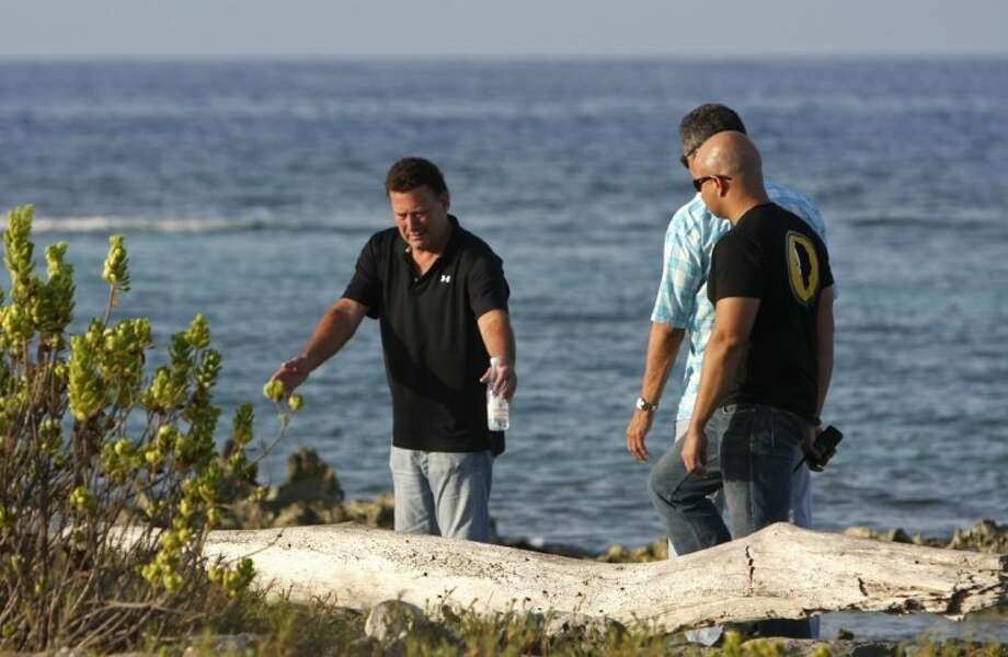 In this picture taken Aug. 3, Gary V. Giordano, left, speaks with Aruba's police detectives as they search for his travel partner Robyn Gardner, 35, of Frederick, Maryland, at Baby Beach in the southern tip of the Caribbean island.