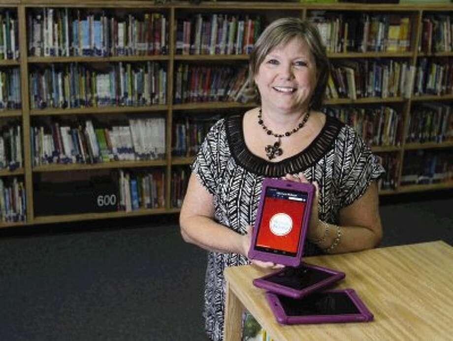 Pat Perez is Parmley Elementary School's new information learning specialist. Current library professionals will be information and instructional leaders both in the library and throughout their campus. Perez and other librarians will use a variety of digital technologies to encourage students to read, including the Google Nexus. Photo: Staff Photo By Jason Fochtman / Conroe Courier