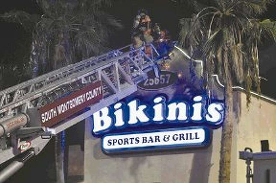 South Montgomery County firefighters climb a ladder in an effort to put out a fire at Bikini's in South County. Photo: Keith MacPherson
