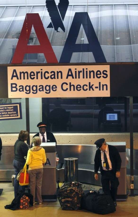 In a Feb. 1 photo, American Airlines baggage handlers help passengers check luggage at Dallas-Fort Worth International airport in Grapevine. Pilots rejected the company's final contract offer Wednesday. Photo: LM  Otero