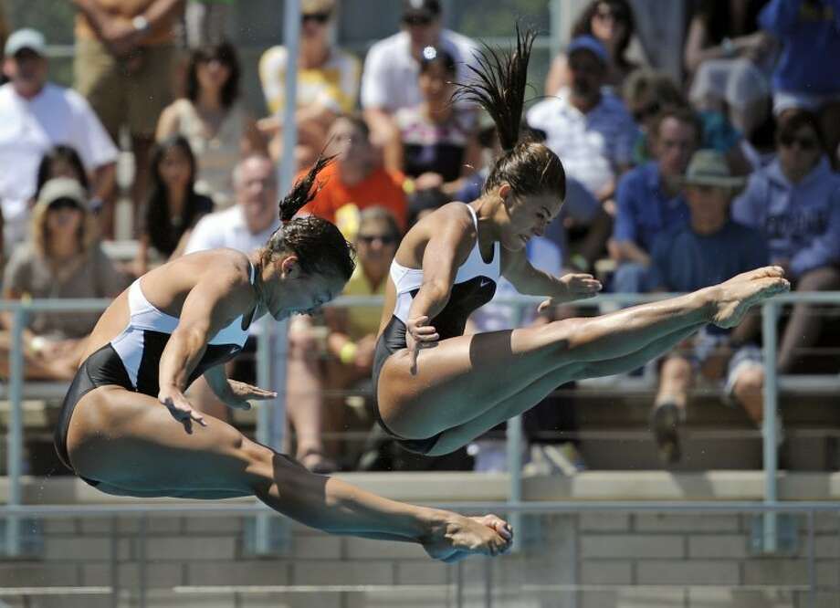 Cassidy Krug, left, and Kassidy Cook, a junior at The Woodlands High School,dive during the women's synchronized 3-meter springboard finals at the 2011 AT&T National Diving Championships, Saturday in Los Angeles. The pair won the event. Photo: Mark J. Terrill