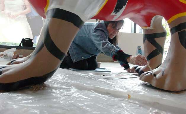 "Francine Funke puts sandals on her ""3 Dog Knight"" at the Artist's Studio at 1 Landmark Sq in Stamford Downtown Monday morning, May 3, 2010.  Funke joins other artists working on the twenty-three dogs and seventeen cats that have arrived for the DSSD's upcoming Summer sculpture exhibit, ""It's Reigning Cats & Dogs."" Photo: Keelin Daly / Stamford Advocate"