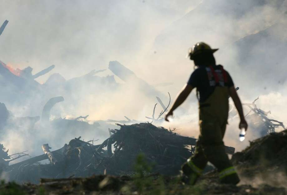 A firefighter walks across the scene of a large mulch yard fire Saturday on Highway 242 East in Conroe.