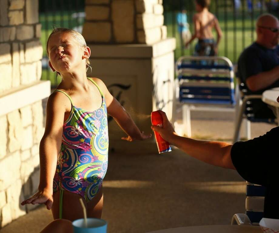 In this Tuesday photo, residents spray insect repellent on themselves and others at National Night Out at The Fairways community pool in Frisco. Cases of West Nile virus are on the rise in North Texas. Photo: Tom Fox
