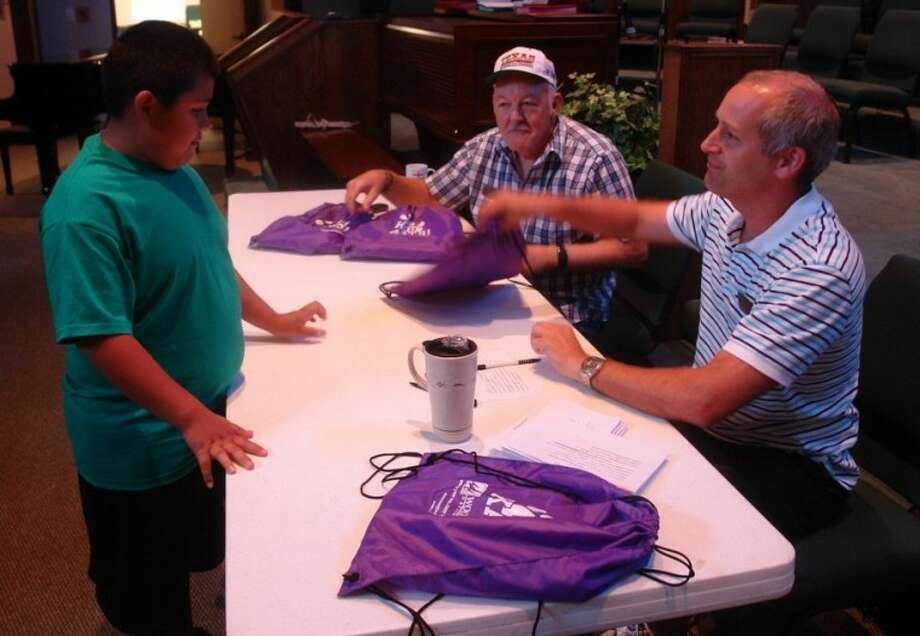 "A ninth-grade student from the Willis independent School District receives a bag full of school supplies Saturday morning, courtesy of the First United Methodist Church in Willis as part of their annual School Supply Giveaway. Over 500 bags with ""Go Kats"" logos were ready to be handed out to students from 8 a.m. to 11 a.m. inside the church's Family Life Center."