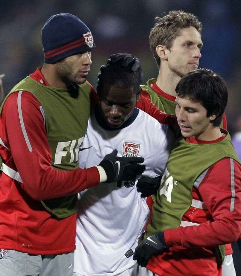 Maurice Edu, center, is comforted by teammates at the end of the World Cup round of 16 soccer match between the United States and Ghana at Royal Bafokeng Stadium in Rustenburg, South Africa, Saturday. Ghana won 2-1, advancing to the World Cup quarterfinals. / AP