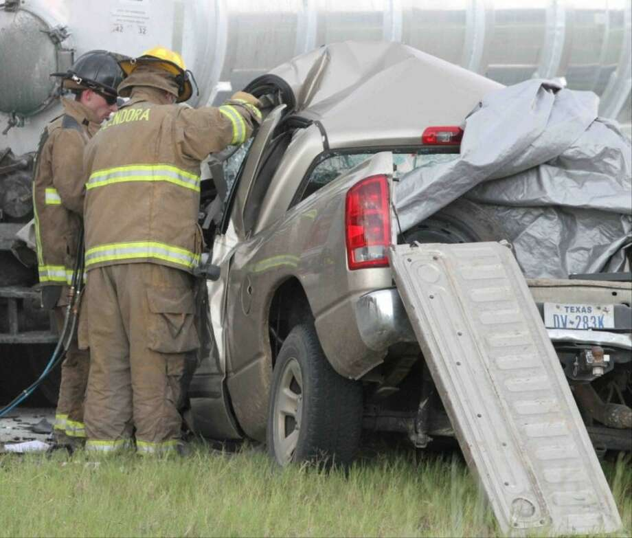 Police officers and firefighters work an accident scene on U.S. 59 off East River Road Friday afternoon in Splendora.