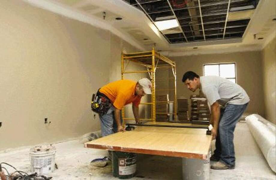 Workers lay down a door after un-installing it at First Baptist Church of Conroe Friday. Photo: Staff Photo By Jason Fochtman / Conroe Courier