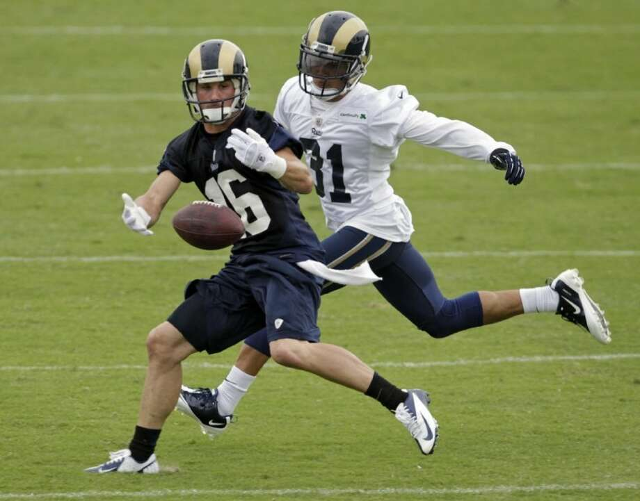 St. Louis Rams wide receiver Danny Amendola reaches out to catch the ball as he is defended by defensive back Cortland Finnegan during training camp July 30 in St. Louis. Photo: Tom Gannam