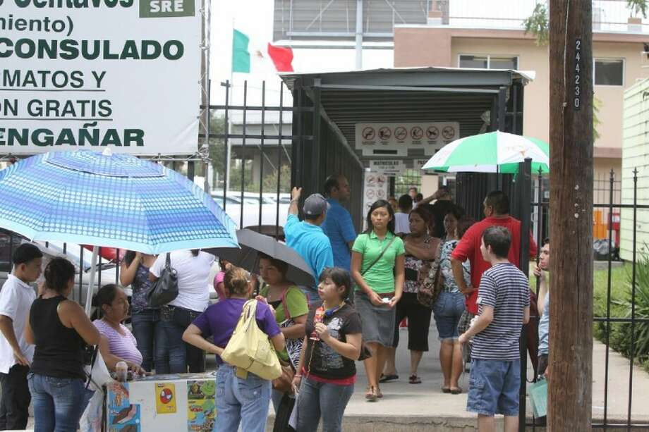 Families wait to turn in paperwork for President Obama's Deferred Action immigration program outside the Mexican Consulate office in Houston Wednesday. Photo: Photo By Alan Warren