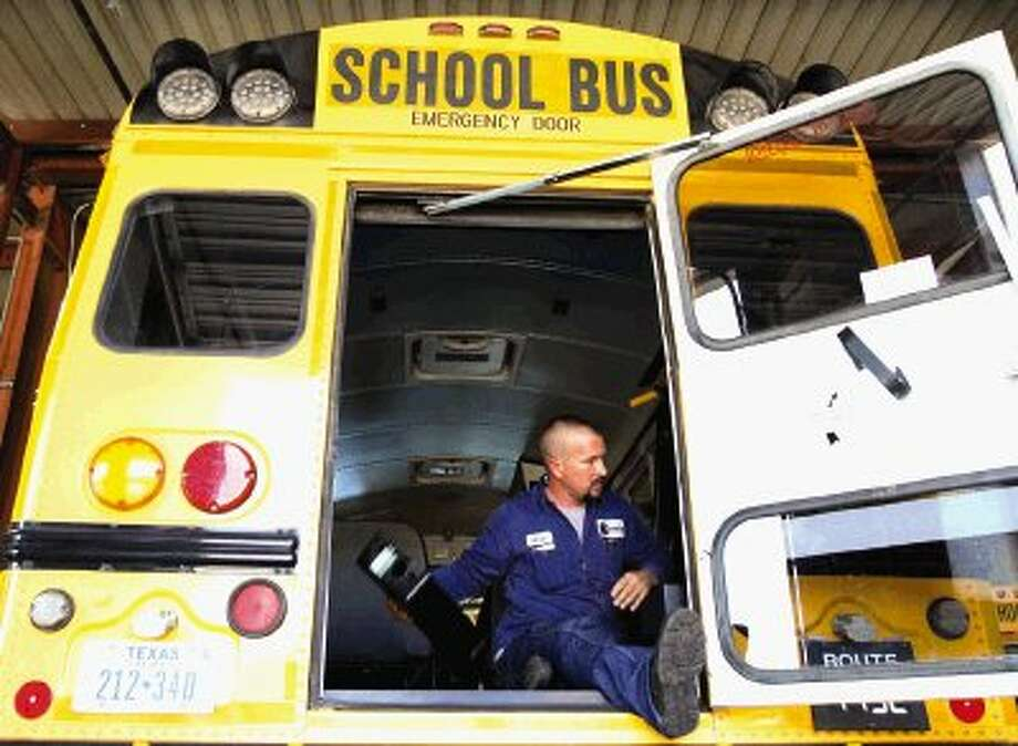 Mechanic Kevin Prater works on a school bus at the Conroe ISD Transportation Center Friday. About 175 to 200 buses are serviced each day during the school year at the center.