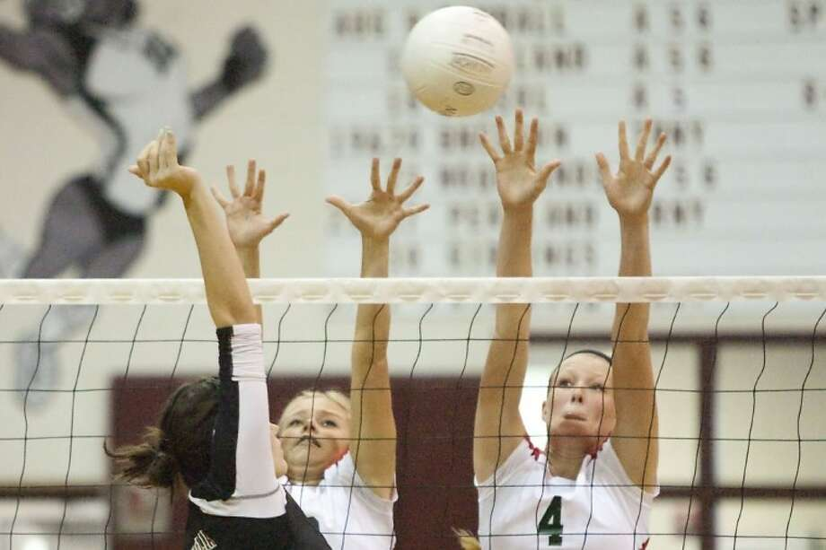The Woodlands' Riley Johnson and Maddie Slater go for a block against Magnolia's Chelsea Reynolds during a non-district match Tuesday at Magnolia High School. Photo: Karl Anderson