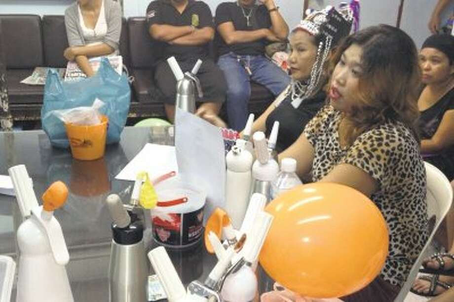 Thai vendors are shown at a police news conference with laughing gas balloons, foreground, following their arrest in Bangkok, Thailand on August 24. Thai authorities are cracking down on vendors in Bangkok's main backpacker district selling cheap doses of balloons filled with nitrous oxide, or laughing gas, to tourists.