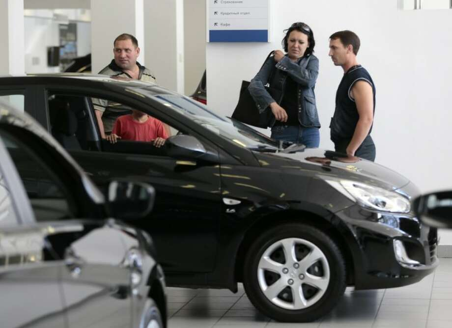 Visitors look at a car in a car dealership in Moscow Wednesday. After 19 years of negotiation, Russia entered Wednesday the World Trade Organization, which restricts import duties and subsidies in an attempt to create a truly level playing field for international trade. Photo: Ivan Sekretarev