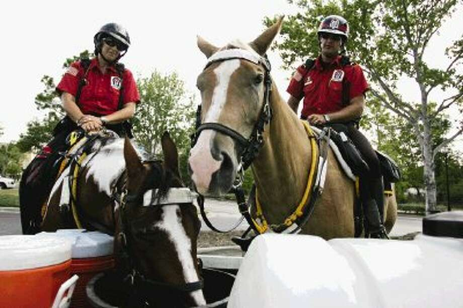 Alpha & Omega Mounted Patrol Troopers Curtis Hilliard, right, with horse Rio, and Lori Williamson with horse Jenny, take a water break Wednesday at The Woodlands Mall. Temperatures are expected to top 100 degrees through the weekend.