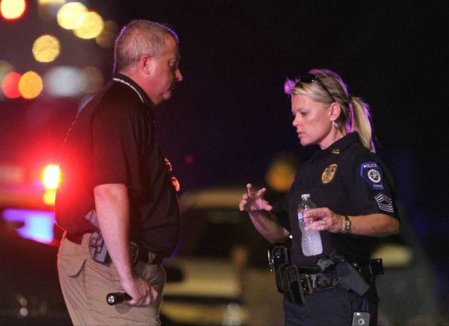 Sgt. Dorcy Riddle, public information officer with the Conroe Police Department, talks to a crime scene investigator at the scene of a shooting near the Conroe Wal-Mart off Loop 336 Wednesday evening. To view more photos go to HCNPics.com Photo: Staff Photo By Jason Fochtman