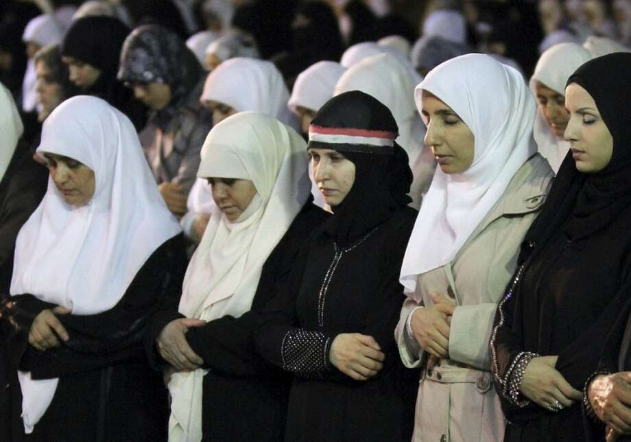Syrian women, who live in Amman, Jordan, perform Ramadan special prayers before a rally calling for President Bashar Assad to step down, in Amman, Jordan, Friday, Aug. 26, 2011. Woman at centre bears a Syrian flag upon her head scarf. (AP Photo/ Nader Daoud) Photo: Nader Daoud