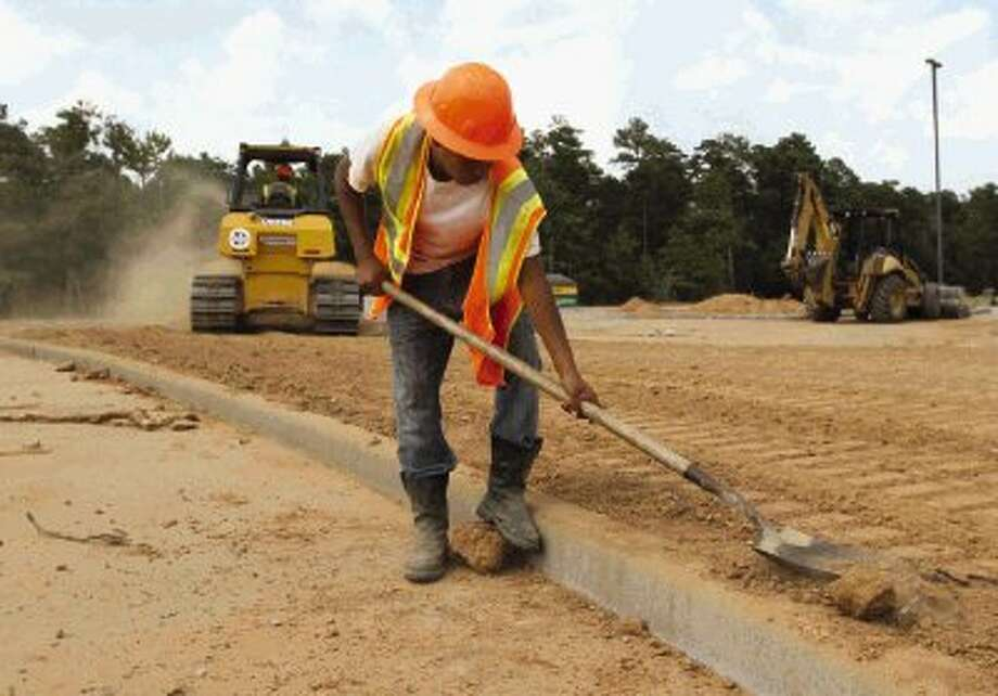 A worker levels dirt on a parking lot under construction at the new Conroe High School Ninth Grade School in Conroe Thursday. The $24 million renovation is expected to be completed by Aug. 13. / Conroe Courier