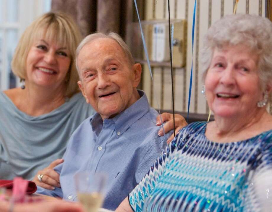Don Price, center, smiles alongside his daughter Bonnie Price Day, left, and wife Vera Price as he celebrates his 100th birthday Saturday at the Carriage Inn Retirement Living Center in Conroe. Photo: Staff Photo By Eric Swist