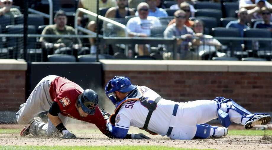 The Houston Astros' Marwin Gonzalez, left, slides past home plate as New York Mets catcher Kelly Shoppach applies the tag in the ninth inning. The Mets won 2-1. Photo: Craig Ruttle