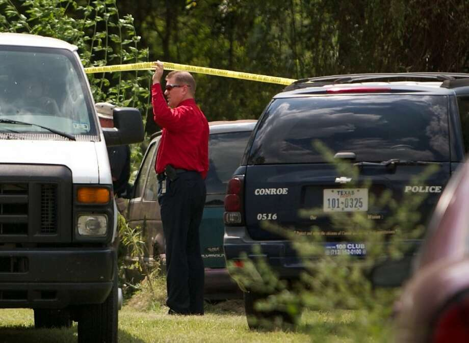 Conroe police investigators examine the scene where skeletal remains were found Tuesday on Criminal Justice Drive in Conroe. Photo: Staff Photo By Eric Swist