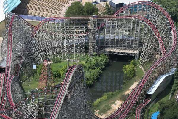 This July 20, 2013, file aerial photo shows the Texas Giant roller coaster at Six Flags Over Texas, in Arlington, Texas. The death of a woman who fell 75 feet from Six Flags Over Texas' Texas Giant roller coaster is reinvigorating discussion among safety experts about whether it's time to create more consistent, stringent regulations for thrill rides across the nation.