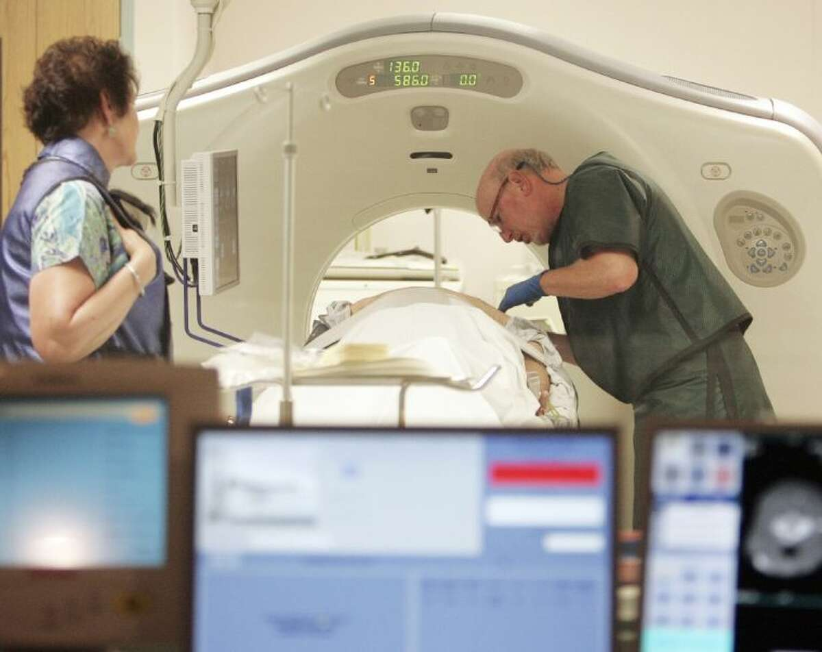 In this June 3, 2010, file photo, Dr. Steven Birnbaum works with a patient in a CT scanner at Southern New Hampshire Medical Center in Nashua, N.H. A national study suggests the world's top cancer killer isn't always as deadly as doctors once thought, finding that more than 18 percent of lung cancers detected in screening scans are likely so slow growing that they'd never cause problems.