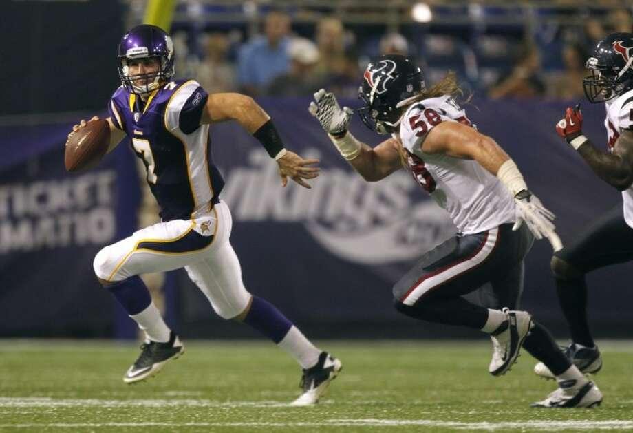 Minnesota Vikings quarterback Christian Ponder runs from Houston Texans linebacker Brooks Reed during the first half Thursday in Minneapolis. Photo: Andy King