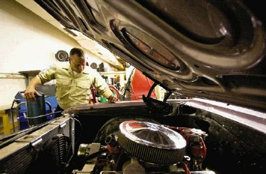 Conroe High School Auto Tech Instructor Brian Courtney peers into the engine bay of a classic car that students worked on last year. The Automotive Technology program at the high school is receiving new tools and an expanded space. Photo: Staff Photo By Eric Swist