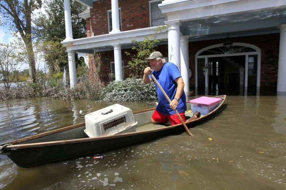 Don Duplantier paddles a pirogue from his flooded home as floodwaters from Hurricane Isaac recede in Braithwaite, La. Sunday. Duplantier had retrieved his cat and had collected his daughter's bridesmaid dress for the upcoming wedding of his son. Photo: Gerald Herbert
