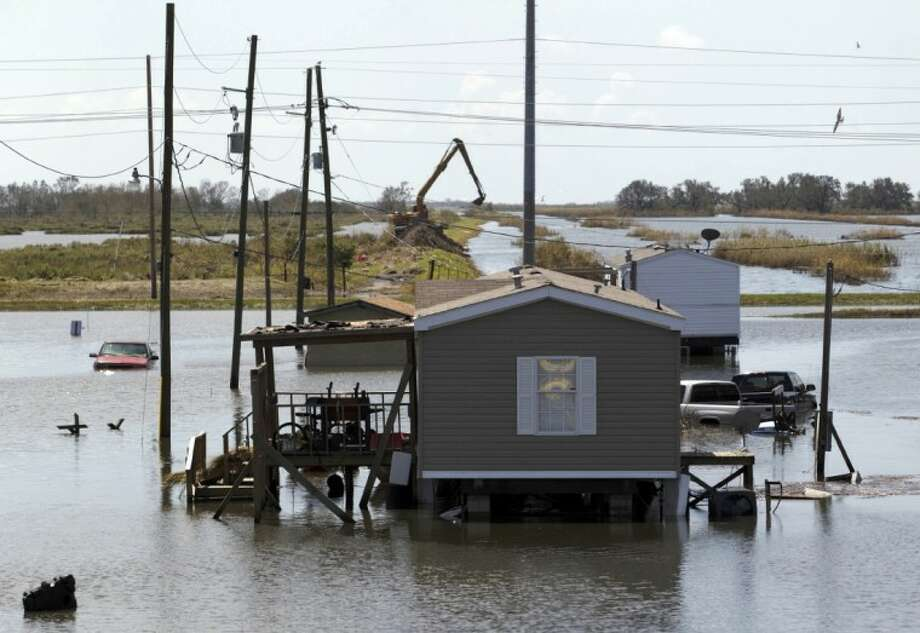 Trucks are flooded in receding waters from Hurricane Isaac along Louisiana Hwy 23 near West Point a La Hache, La., Monday. Photo: Matthew Hinton