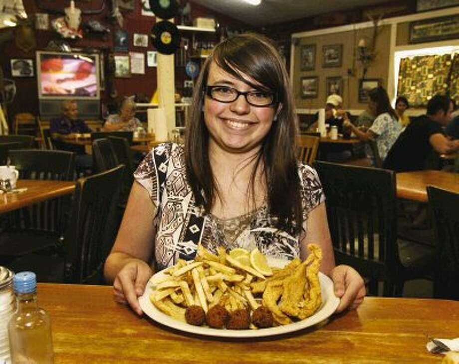 Courier summer intern, Candice Nichols, 16, displays a large platter of fried catfish and a double order of fries -- which she finished at the Fish Pond.