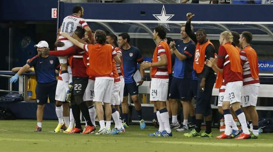 Teammates congratulate the United States' Landon Donovan after he scored a goal against Honduras during the first half of the Gold Cup semifinals on Wednesday at Cowboys Stadium in Arlington. Photo: Brandon Wade