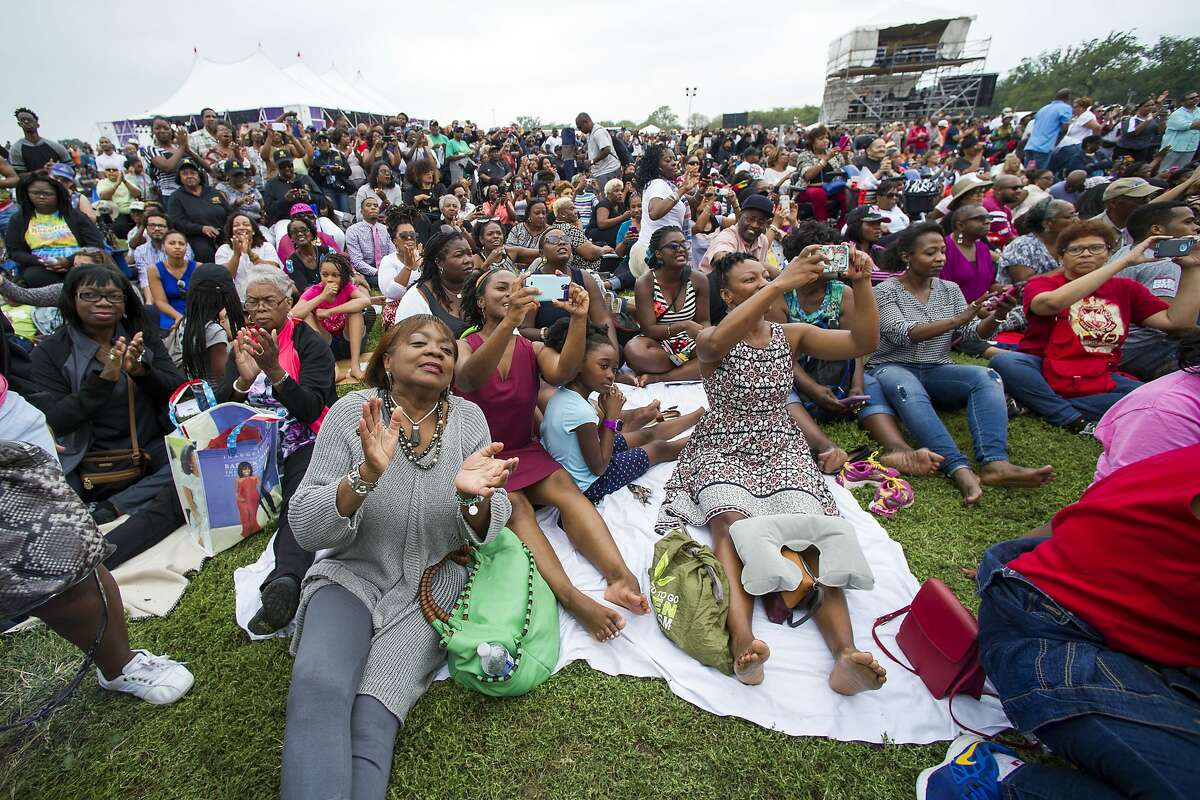 People sit on the Washington Monument grounds in Washington, Saturday, Sept. 24, 2016, and watch a large video monitor at the dedication and opening ceremony of the Smithsonian's National Museum of African American History and Culture. (AP Photo/Cliff Owen)