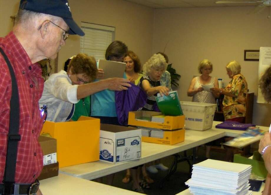 More than 20 First United Methodist Church of Willis volunteers, including several members of the youth group, filled 600 backpacks with school supplies for Saturday's event. Pictured in the center are Linda McKeon, shopper for the school supplies, and volunteer Carrolyn Breeden.