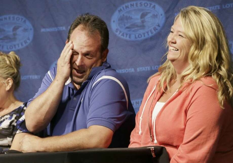 Paul White, of Ham Lake, Minn., gets a laugh from his girlfriend Kim VanReese, right, as he talks about his plans after he was announced one of the winners of the $448.4 million Powerball Jackpot Thursday in Minneapolis. White's share of the jackpot is $149.4 million. The woman at left is a co-worker friend.