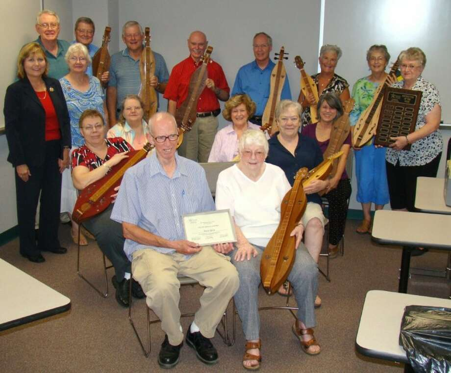Holding her dulcimer, Nancy Price, front right, Lone Star College-Montgomery's Academy for Lifelong Learning's Instructor of the Year, is surrounded by current and former dulcimer students.