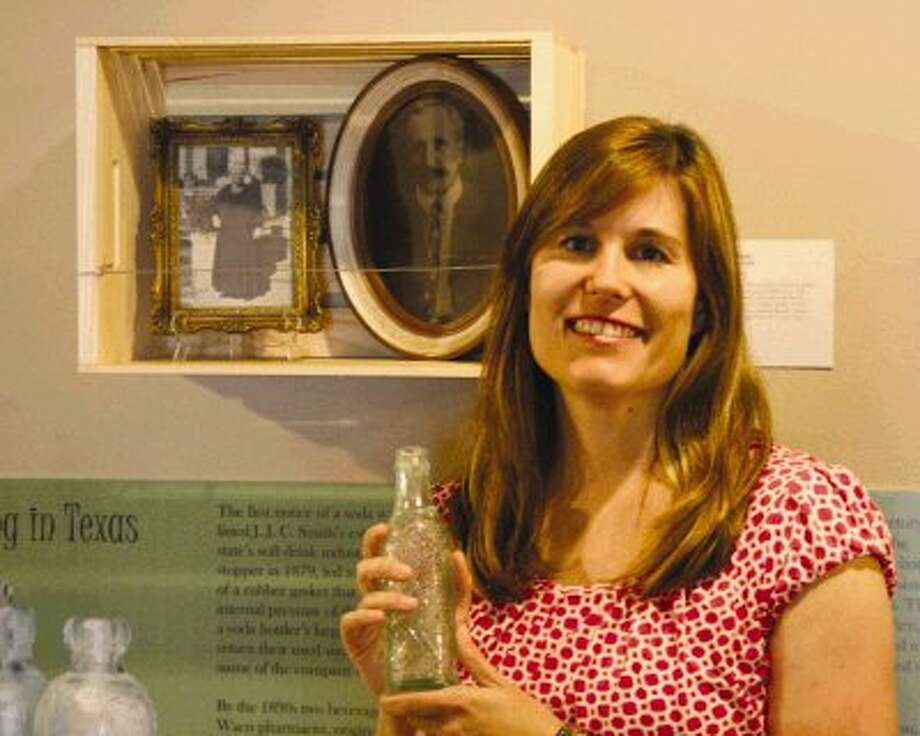 """The Heritage Society at Sam Houston Park in downtown Houston features the """"Bitters, Brews and Beyond"""" exhibit through Oct. 26. Collections Manager for The Heritage Society, Ginger Berni, is pictured with a bottle from the exhibit."""