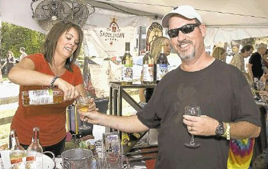 Karla Nash, owner of Cork This! winery in Montgomery, fills the glass of a visitor at the annual Historic Montgomery Wine & Music Fest -- set for Sept. 21. / @WireImgId=2596394
