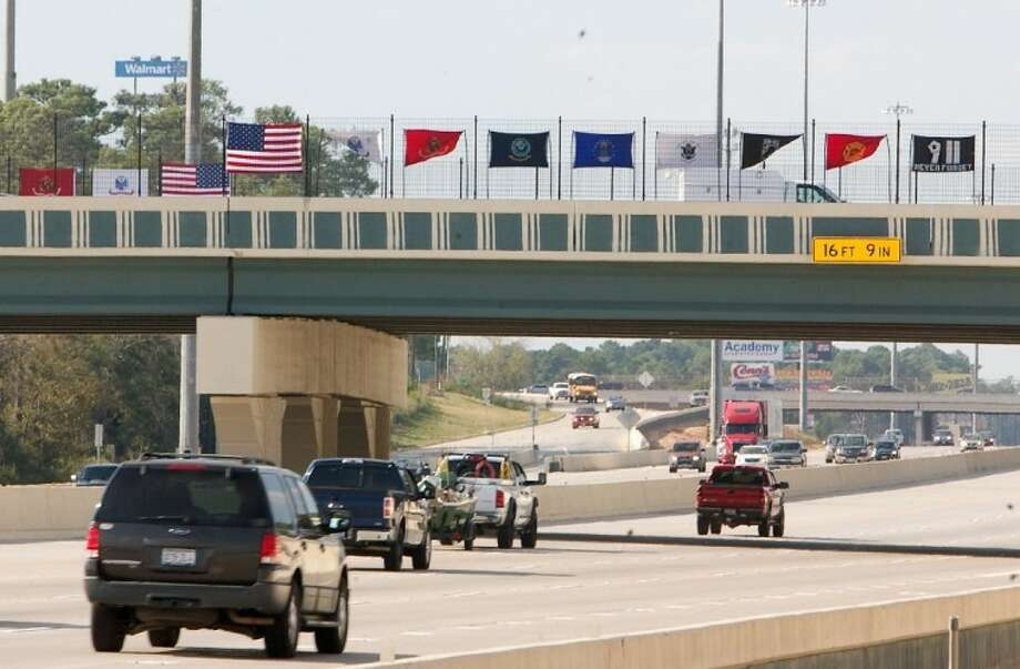 Flags are seen hung across the Wilson Road Overpass - now known as the Veterans Memorial Bridge - in a tribute to the victims lost in the 9/11 terrorist attacks. Photo: Staff Photo By Eric Swist